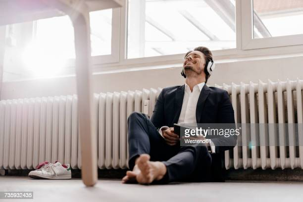 Businessman with tablet and headphones sitting on floor
