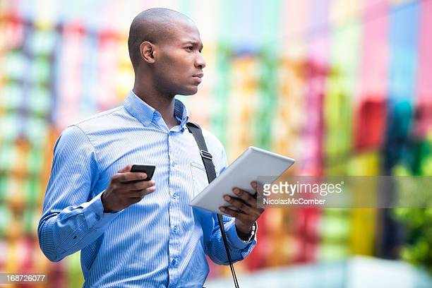 Businessman with tablet and smart phone looking away