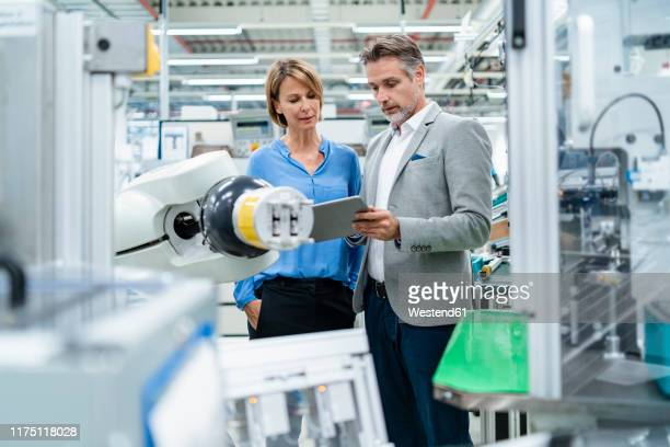 businessman with tablet and woman talking at assembly robot in a factory - robotic arm stock pictures, royalty-free photos & images