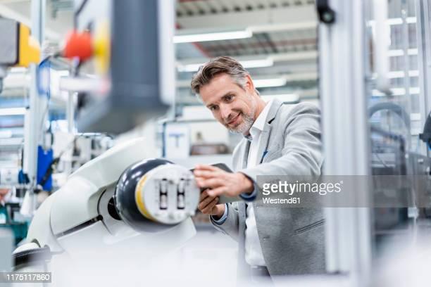 businessman with tablet at assembly robot in a factory - rechnerunterstützte fertigung stock-fotos und bilder