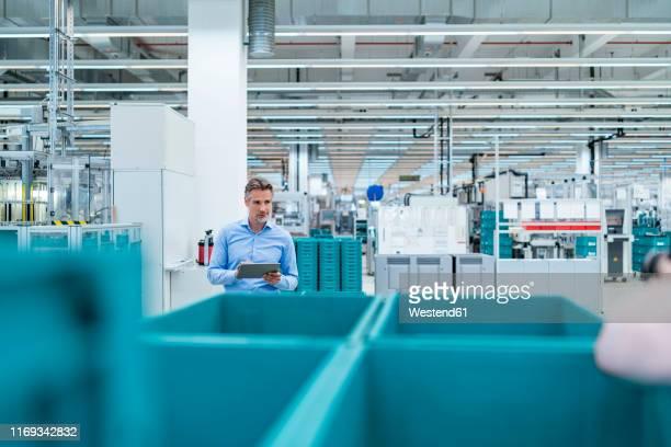 businessman with tablet in a factory hall - fracht stock-fotos und bilder