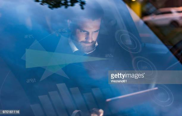 Businessman with tablet in car at night surrounded by data