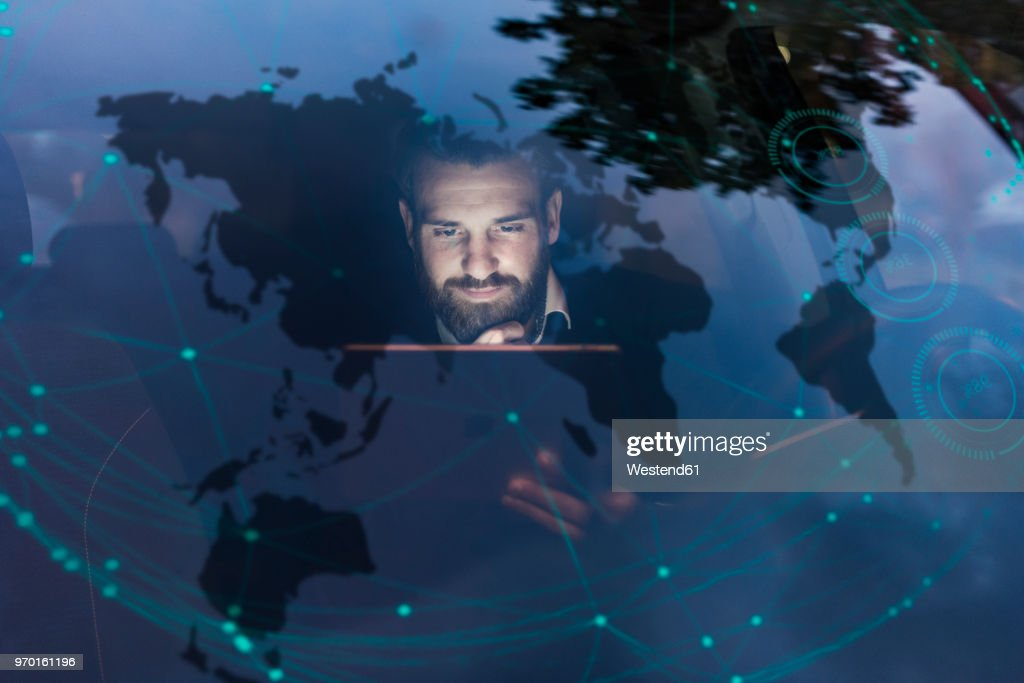 Businessman with tablet in car at night surrounded by data : Foto stock