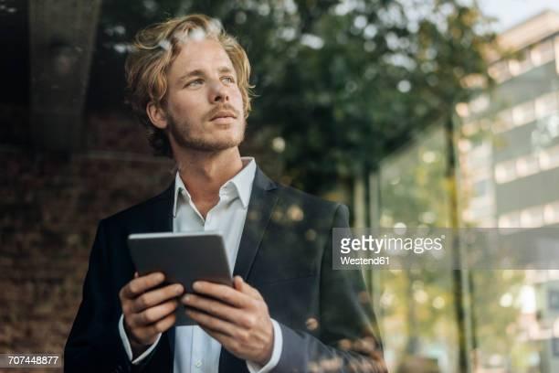 businessman with tablet looking away - freischaffender stock-fotos und bilder