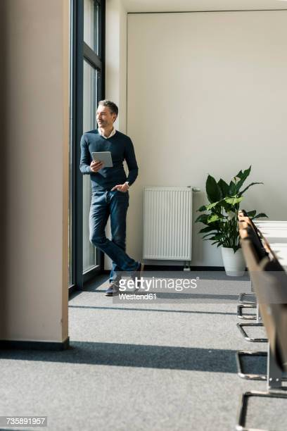 Businessman with tablet standing in a conference room looking through window