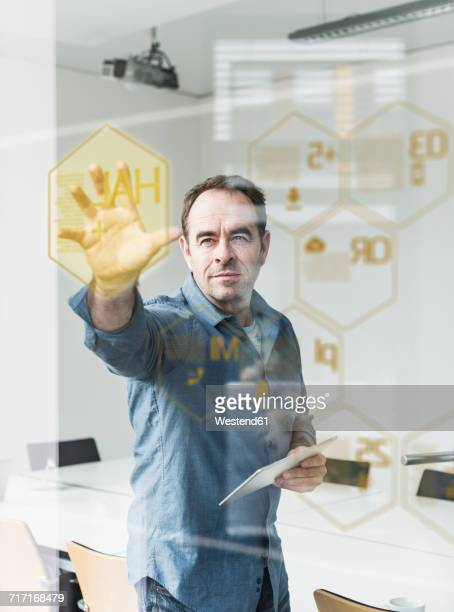 Businessman with tablet touching glass pane with data in office