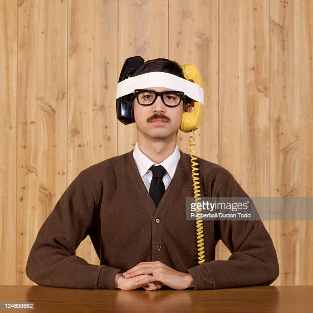 Businessman with telephones strapped to head in office