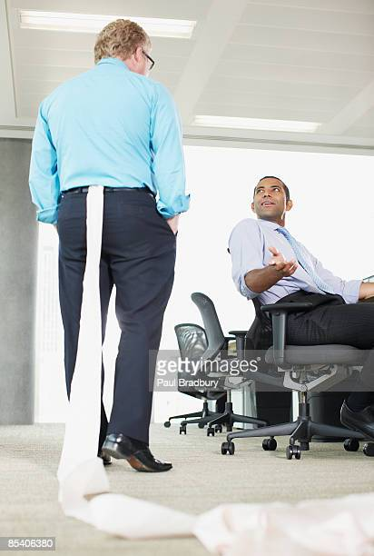 Businessman with toilet paper stuck in his pants