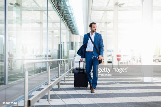 businessman with trolley and smartphone at airport - geschäftsreise stock-fotos und bilder