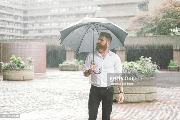 Geschäftsmann mit Regenschirm im Regen