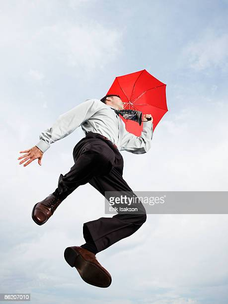 Businessman with umbrella jumping in mid-air