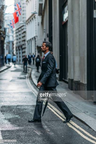 Businessman with umbrella on rainy day in London, UK
