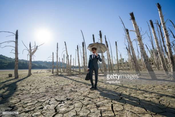 geschäftsmann mit regenschirm auf rissige erde stehend - klimaschutz stock-fotos und bilder