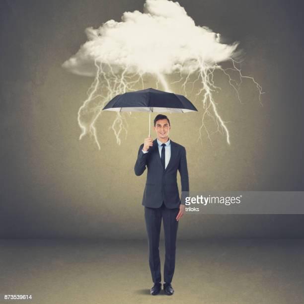 Geschäftsmann mit Regenschirm unter Gewitterwolke