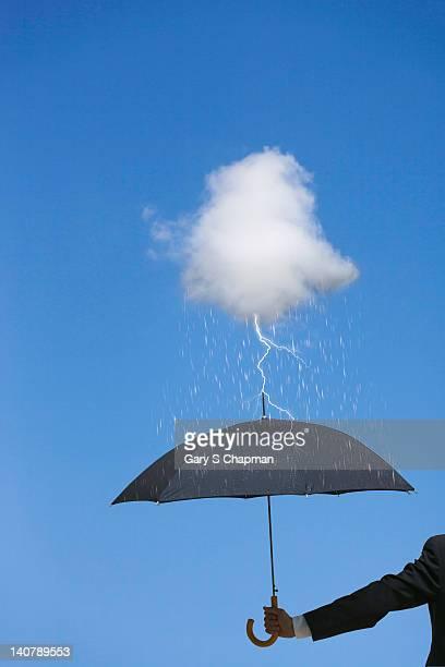 Businessman with umbrella under tiny storm cloud