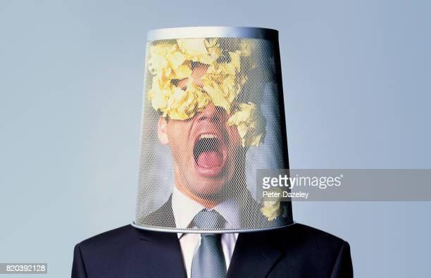 Businessman with waste paper bin on head