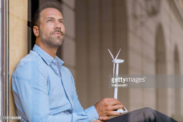 businessman with wind turbine model behind windowpane thinking - one man only stock pictures, royalty-free photos & images
