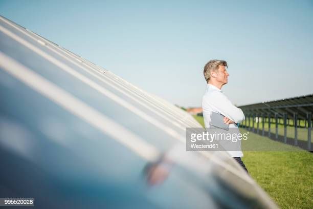 businessman with wireless earphone using tablet at solar park - alternative energiequelle stock-fotos und bilder