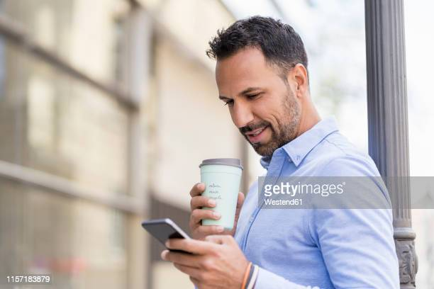 businessman with with takeaway coffee and cell phone in the city - shirt stock pictures, royalty-free photos & images