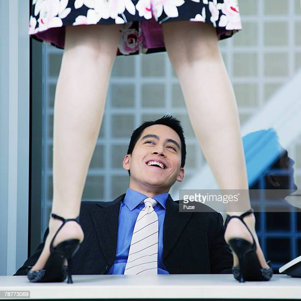 Businessman with Woman Standing on Desk