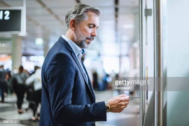 Businessman withdrawing money at an ATM in the city
