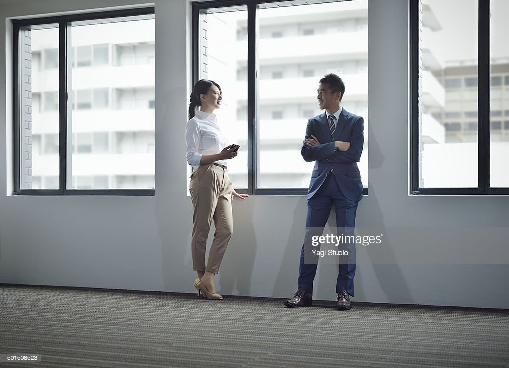 Businessman & woman standing by windows : Stock Photo