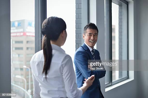 businessman & woman standing by windows - ホワイトカラー ストックフォトと画像