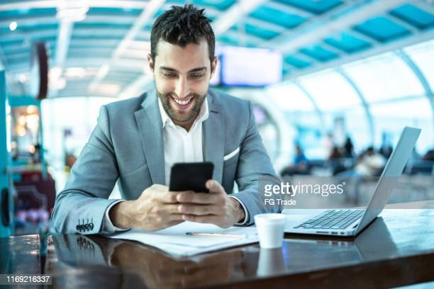 zakenman werkt en gebruikt mobiel op koffie tijd op luchthaven - mobile stockfoto's en -beelden