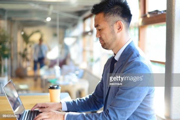 カフェのカウンターで働くビジネスマン - ビジネスマン ストックフォトと画像
