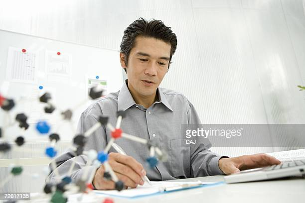 Businessman working at desk, chemical model in foreground, low angle view, differential focus