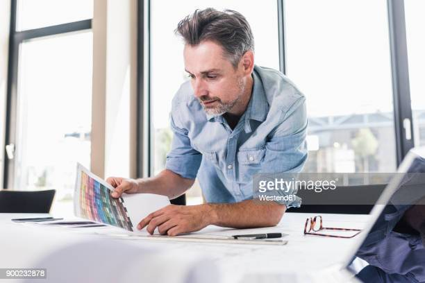 businessman working at desk in office - printed media stock pictures, royalty-free photos & images