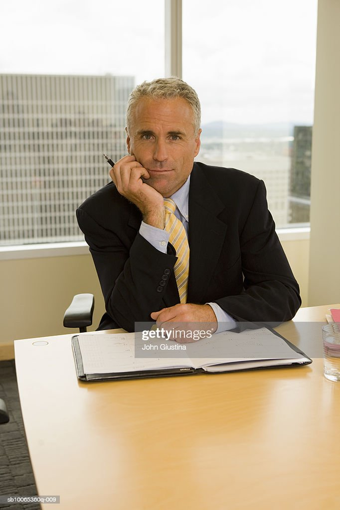 Businessman working at desk, smiling, portrait : Foto stock