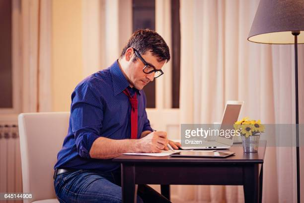 Businessman working at home, late night work exhausts but brings results