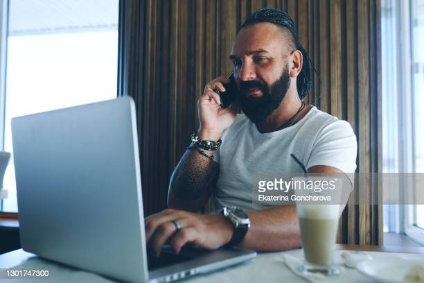 businessman working from cafe on laptop and phone - part of a series stock pictures, royalty-free photos & images