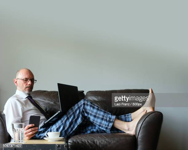 businessman working from home on couch in dress shirt and pyjama pants with laptop and mobile smartphone, stuttgart, germany - pyjamas stock pictures, royalty-free photos & images