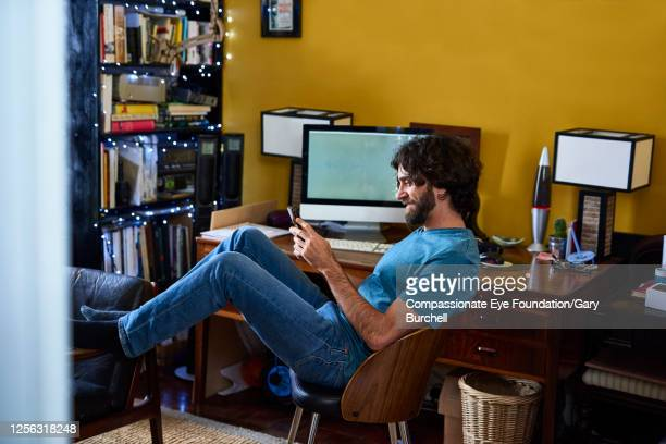 businessman working from home using cell phone - real people stock pictures, royalty-free photos & images
