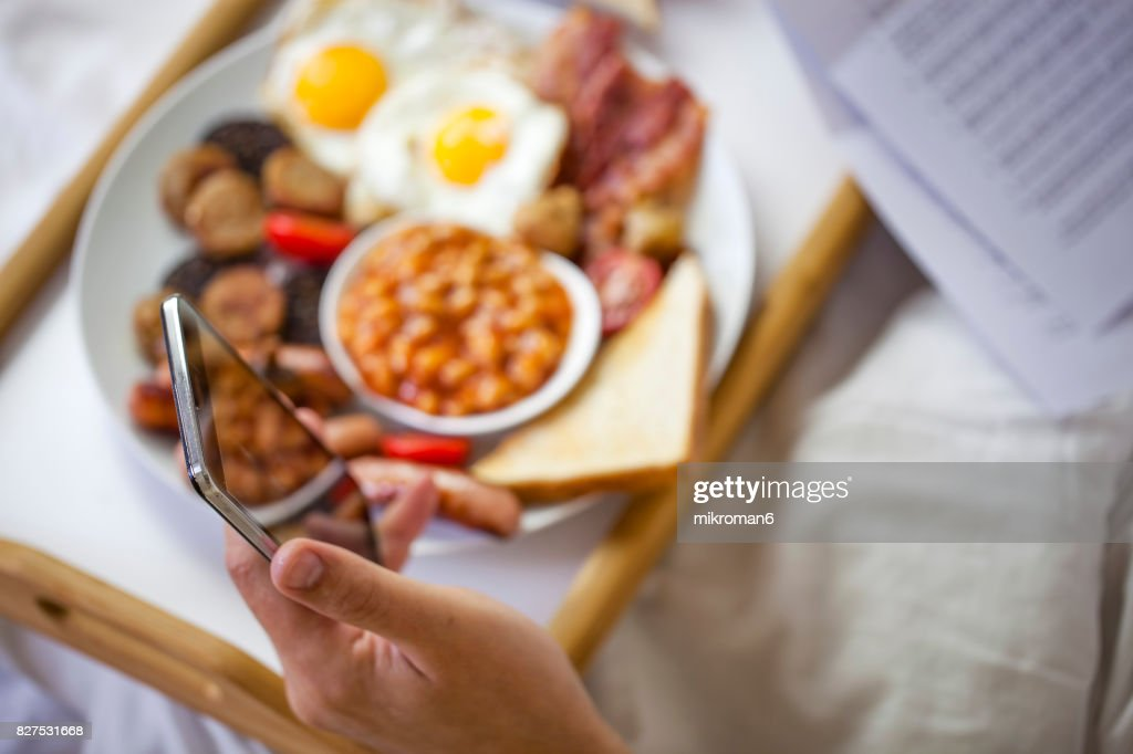 Businessman working in bed and eating  Irish breakfast on tray. : Stock Photo