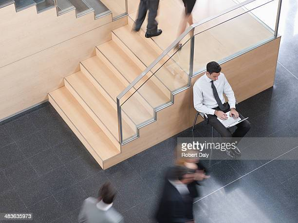 Businessman working in busy office corridor