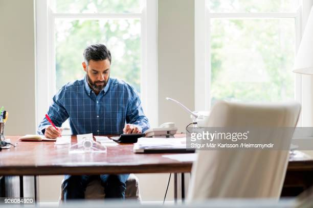businessman working in home office - calculator stock photos and pictures