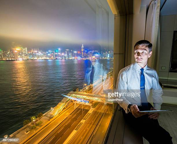Businessman working in Hotel room Hong Kong skyline