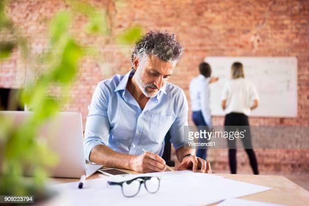 Businessman working in office with colleagues in background