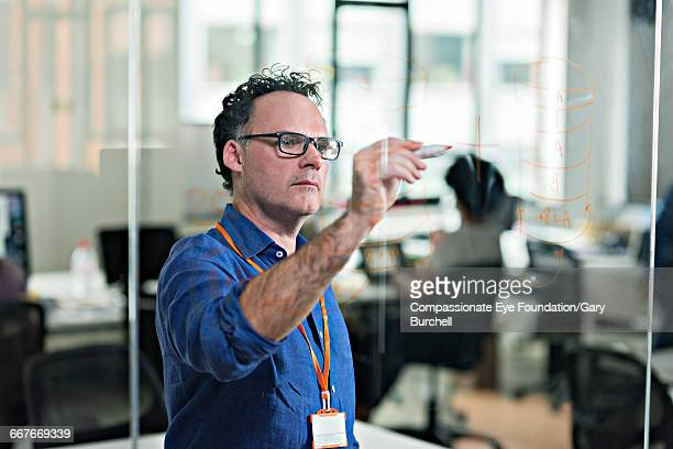 businessman working in tech start-up office - compassionate eye foundation stock pictures, royalty-free photos & images