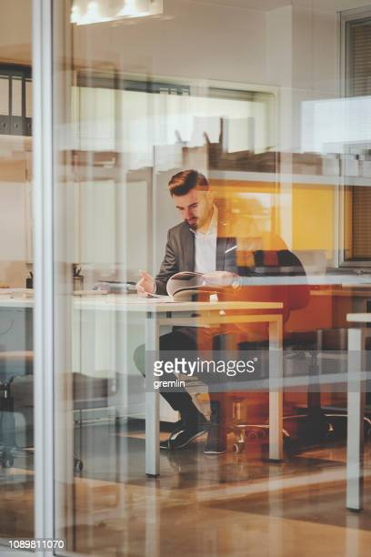 businessman working in the office - glass magazine stock photos and pictures