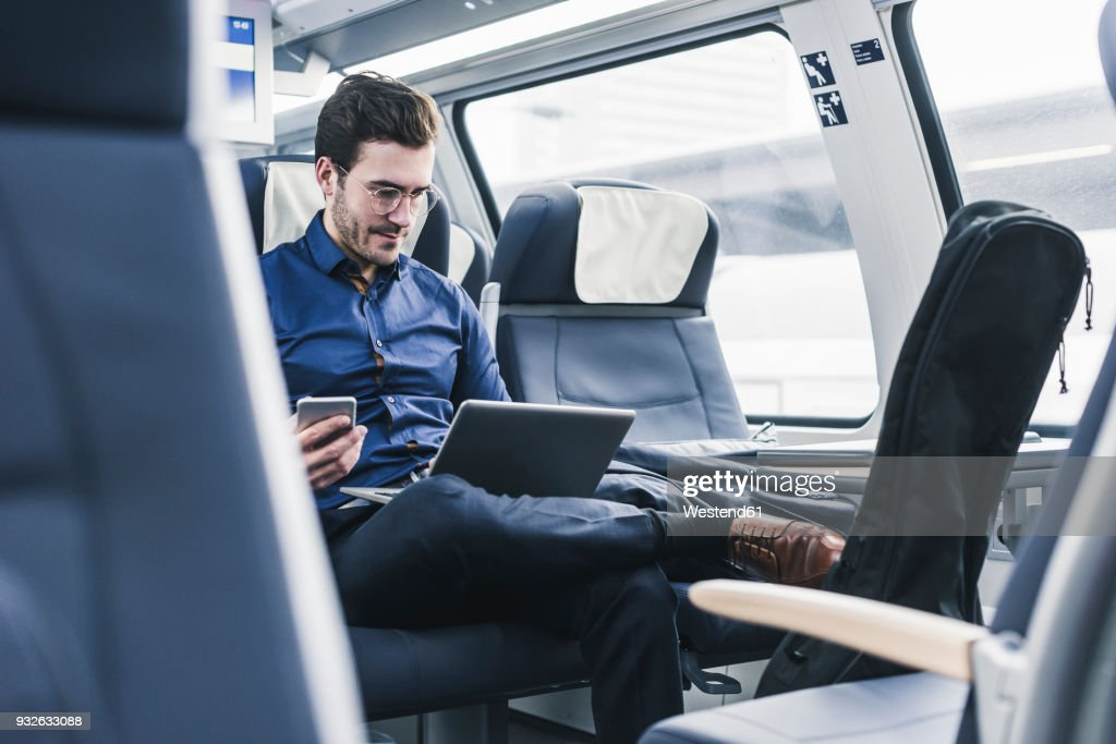 Businessman working in train using laptop : Stock Photo