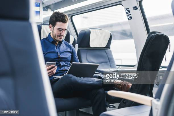 businessman working in train using laptop - train stock photos and pictures