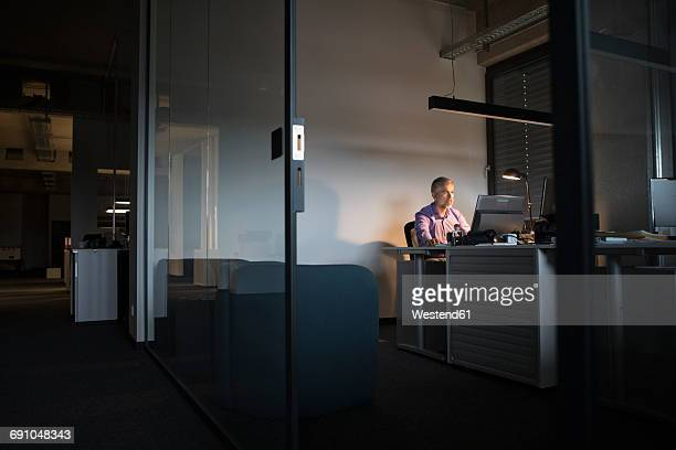 businessman working late in office - angle poise lamp stock pictures, royalty-free photos & images