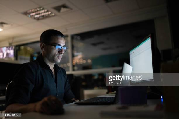 homem de negócios que trabalha tarde no escritório - reflexo efeito de luz - fotografias e filmes do acervo