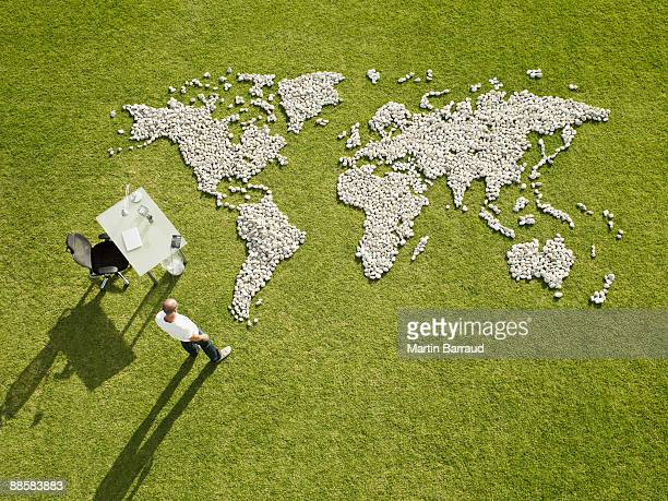 Businessman working near world map made of rocks