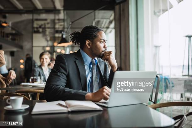 businessman working on a coffee break - full suit stock pictures, royalty-free photos & images