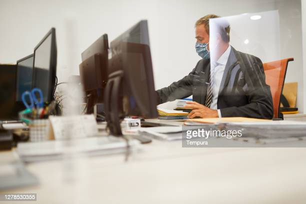 un homme d'affaires travaillant sur un ordinateur de bureau - affaires finance et industrie photos et images de collection